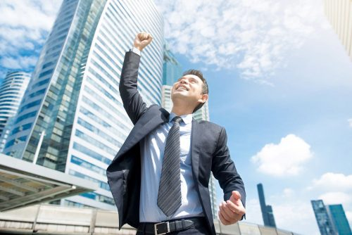 A man lifting his arms in front of a building under a blue sky